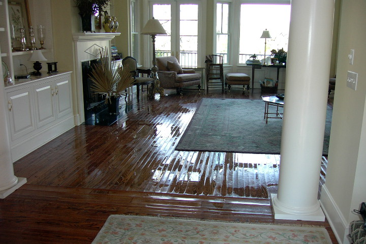 image of living room that was flooded and DisasterCare is drying the hardwood floor